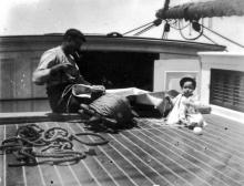 Baby on shipboard with a seaman who is repairing a sail